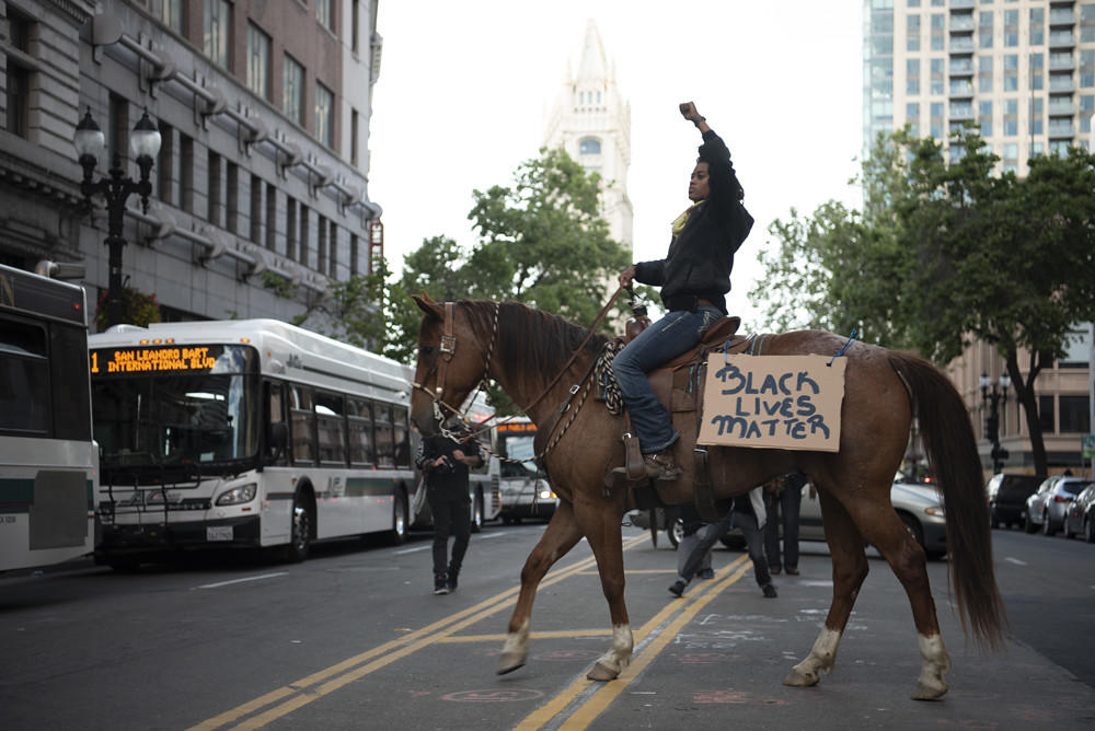 Brianna Noble riding her horse Dapper Dan in Oakland with AC Transit buses in the background