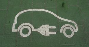 White outline of a car with an electric plug painted on green pavement to mark electric vehicle charging.