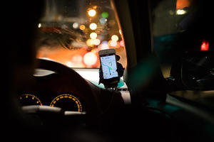 Interior of a cart at night with a smartphone mounted on the dash displaying Uber directions for the driver.