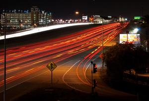 I-580 at night where car head and tail lights blur together in red and white streaks.