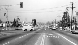 Black and white picture of a white van in the intersection of Newport Ave. at First St., Tustin, April 1966