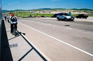 Picture of cyclists riding on the sidewalk of Tassajara Road over 580 in Dublin with cars driving in the road.