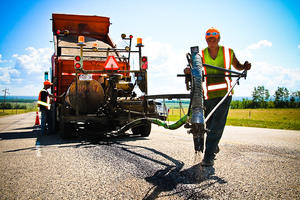 Workers using machinery to apply a seal coat to cracks in asphalt pavement.