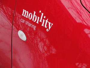 "Close up image of ""mobility car sharing"" painted in white on a red car."