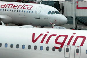 Two Virgin America A320s on the tarmac at an airport terminal.